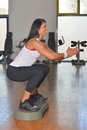 Young woman doing fitness exercises on stepper at gymnasium Stock Photos