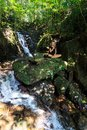 Young woman doing meditating enjoying in yoga pose in waterfall Stock Image