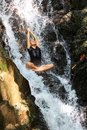 Young woman doing meditating enjoying in yoga pose in waterfall Royalty Free Stock Image