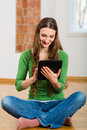 Young woman doing online dating sitting at home on the floor and buying new furniture over the internet using a tablet computer Stock Photos