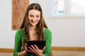 Young woman doing online dating sitting at home on the floor and buying new furniture over the internet using a tablet computer Royalty Free Stock Photos