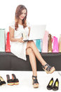 Young woman doing online transaction and sitting between shoppin Royalty Free Stock Photo