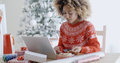 Young woman doing Xmas shopping online Royalty Free Stock Photo
