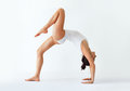Young woman doing yoga asana bridge pose with right leg up Royalty Free Stock Photo