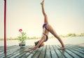 Young woman doing yoga in bikini on wooden river raft