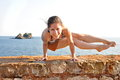 Young woman doing yoga pose at the sea Royalty Free Stock Photos