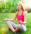 Young woman doing yoga in summer park attractive Stock Image
