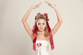 Young woman in a doll style with red bows holding her hands up studio shot Royalty Free Stock Image