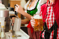 Young woman drawing beer in restaurant or pub she is the innkeeper Stock Photos