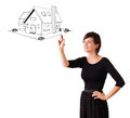 Young woman drawing a house on whiteboard Royalty Free Stock Photo