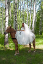 Young woman in the dress of fiancee on a horse Stock Photo