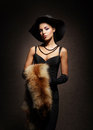 A young woman in a dress with fur rich and beautiful over the vintage background Stock Photography