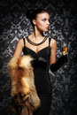 A young woman in a dress holding champagne rich and beautiful with the glass of over the vintage background Royalty Free Stock Photos