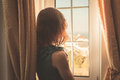 Young woman in dress looking out the window Royalty Free Stock Photo