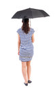 Young woman in dress walking under an umbrella striped dresswalking rear view people collection backside view of person isolated Stock Image