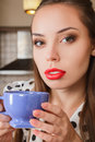 Young woman drink coffee at home or tea against kitchen interior Royalty Free Stock Images