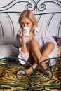 Young woman drinking coffee on the bed Stock Image