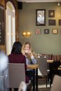 Young woman drinking coffee with female friend portrait of women at coffeeshop Royalty Free Stock Photos