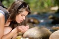 Young woman drinking fresh water from stream in nature close up Royalty Free Stock Photography