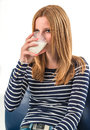 Young woman drinking a glass of milk smiling girl on white background Royalty Free Stock Photography