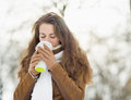 Young woman drinking hot beverage in winter park Royalty Free Stock Image