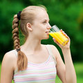 Young woman drinking orange juice. Outdoor Royalty Free Stock Photography