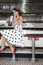 Young woman drinking shake in diner full length side view of a women at the counter Royalty Free Stock Photo