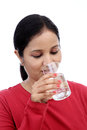 Young woman drinking water against white Stock Photography