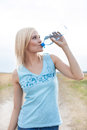 Young woman drinking water from bottle on field Royalty Free Stock Photo