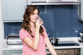 Young woman drinking water in kitchen