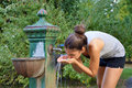 Young woman drinking water from public park fountain. Sport active female adult thirsty after run Royalty Free Stock Photo