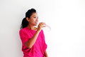 Young woman drinking water and standing against a white wall in pink top Royalty Free Stock Images