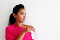 Young woman drinking water and standing against a white wall in pink top Royalty Free Stock Image