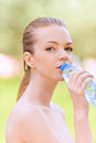 Young woman drinks water from Stock Photography