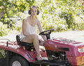 Young woman driving a ride on mower as she cuts the lawn in the garden wearing ear muffs to reduce the sound from the motor Stock Photo