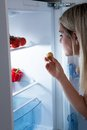 Young woman eating cookies from refrigerator at night Stock Photos