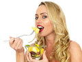Young woman eating fresh fruit salad a dslr royalty free image of an attractive with blonde hair a looking hungry happy and Stock Photography