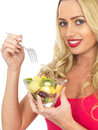 Young woman eating fresh fruit salad a dslr royalty free image of an attractive a looking happy relaxed and excited against a Stock Photos