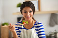 Young woman eating fresh salad in modern kitchen Royalty Free Stock Photo