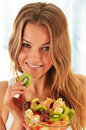 Young woman eating fruit salad Stock Images