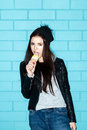 Young woman eating ice cream over blue brick wal in black jacket and cap wall trendy girl having fun indoors lifestyle Stock Photos
