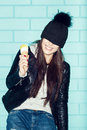 Young woman eating ice cream over blue brick wal in black knit hat wall trendy girl having fun indoors lifestyle Stock Photography