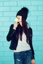 Young woman eating ice cream over blue brick wal in black leather jacket and knit hat wall funky girl having fun indoors lifestyle Stock Photos