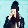 Young woman eating ice cream over blue brick wal in leather jacket and hat wall funky girl having fun indoors lifestyle Royalty Free Stock Image