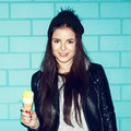 Young woman eating ice cream over blue brick wal pretty in leather jacket and knit hat standing with wall trendy girl having fun Stock Images