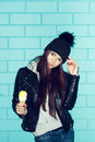Young woman eating ice cream over blue brick wal wall funky girl having fun indoors lifestyle Royalty Free Stock Images