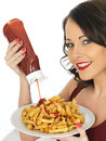 Young Woman Eating a Large Plate of Fried Chips Royalty Free Stock Photo