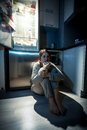 Young woman eating next to refrigerator at night photo of Royalty Free Stock Image