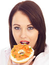 Young Woman Eating Smoked Salmon and Cream Cheese Bagel Royalty Free Stock Photo