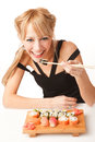 Young woman eating sushi with chopsticks Royalty Free Stock Image